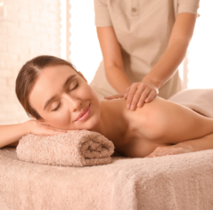 Young woman having body scrubbing procedure with sea salt in spa salon